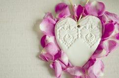 Le coeur blanc en bois ornemental de style de vintage, avec la rose de rose bourgeonne et sur la surface de textile, chic et roma Image stock