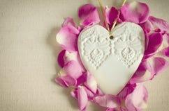Le coeur blanc en bois ornemental de style de vintage, avec la rose de rose bourgeonne et sur la surface de textile, chic et roma Photo stock