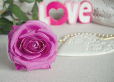 Le coeur blanc en bois ornemental de style de vintage, avec la rose de rose bourgeonne, le mot AMOUR et le collier sur la surface Photos stock