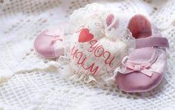 Le coeur blanc fait main de textile avec la maman d'amour de l'inscription I et les petites chaussures de bébé roses sur un blanc Photographie stock libre de droits