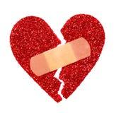 Le coeur brisé. Coeur déchiré par scintillement fixe avec le bandage adhésif Photographie stock libre de droits