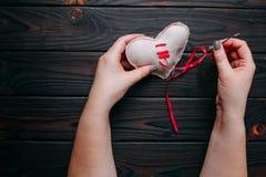 Le coeur brisé curatif Mains cousant un coeur de tissu avec une aiguille Images libres de droits