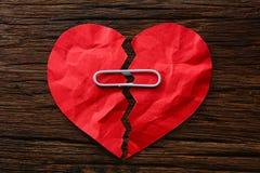 Le coeur brisé de papier avec des trombones sur en bois Photo stock
