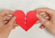 Le coeur brisé de papier sur le fond en bois blanc Photographie stock