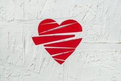 Le coeur brisé de papier sur le fond en bois blanc Image stock