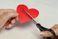 Le coeur brisé de papier sur le fond en bois blanc Photos libres de droits