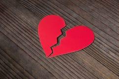 Le coeur brisé de papier sur le fond en bois foncé Photographie stock