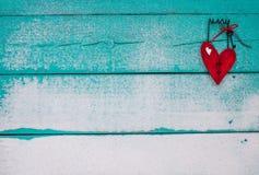 Le coeur brisé en bois rouge accrochant sur le signe arénacé de turquoise Photo stock