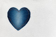 Le coeur classique fait de denim se trouve sur la peau blanche de relief L'espace pour le texte Image libre de droits