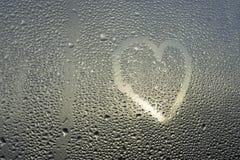 Le coeur coloré lumineux et le mot aiment sur le verre misted humide Photo libre de droits