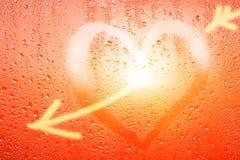 Le coeur coloré lumineux et le mot aiment sur le verre misted humide Photographie stock libre de droits