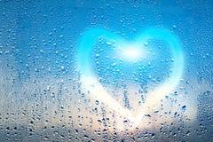 Le coeur coloré lumineux et le mot aiment sur le verre misted humide Photographie stock