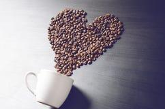 Le coeur consistent des grains de café Le café a rôti des haricots sur une forme comme une tasse de coeur et de café Fond rustiqu Image libre de droits