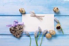 Le coeur décoratif, oeufs, ressort fleurit sur le backgrou en bois bleu Photographie stock libre de droits