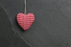 Le coeur de guingan de Valentine rouge d'amour accrochant sur la pierre grise b d'ardoise Photos stock