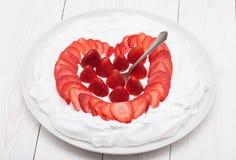 Le coeur de la fraise a fouetté la crème d'un plat Photos libres de droits