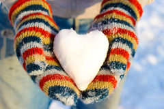 Le coeur de la neige dans votre main, paume dans des mitaines multicolores Images libres de droits
