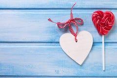 Le coeur de lucette et le coeur décoratif sur le bleu ont peint le pla en bois Image stock
