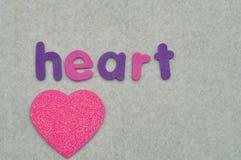 Le coeur de mot avec un coeur rose Photos libres de droits