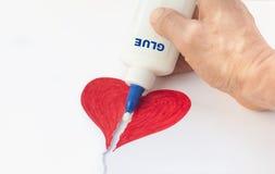 Le coeur de papier cassé est fixé avec la colle dans la main d'un homme image libre de droits