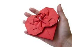 Le coeur de papier rouge d'isolement a fait dans la technique d'origami dans la main femelle sur un fond blanc Concept de l'amour image libre de droits