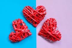 Le coeur de trois rouges en bois handcraft sur le fond de ton de duo Photo libre de droits