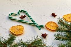 Le coeur des cônes de sucrerie, épices traditionnelles, étoiles d'anis, a séché des oranges sur la table blanche Carte de voeux d Photo libre de droits