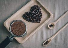 Le coeur des grains de café et des cuillères en bois avec le fabricant de café a préparé sur le bureau Photo libre de droits