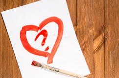 Le coeur dessiné avec la peinture rouge sur une bonne feuille de papier avec a Photo stock