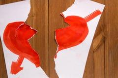 Le coeur dessiné avec la peinture rouge sur une feuille de papier et qui est Photographie stock libre de droits