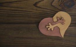 Le coeur deux pièces du puzzle sont joints à la main dans les étreintes sur le fond de la texture Images libres de droits