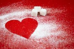 Le coeur du blanc a saupoudré le sucre sur un fond rouge Photographie stock libre de droits