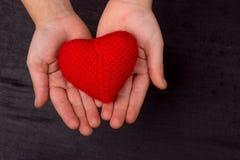 Le coeur du rouge a tricoté le fil de crochet, dans les mains du ` s d'enfants Photographie stock libre de droits