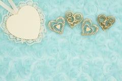 Le coeur en bois avec la dentelle et les coeurs en bois sur la sarcelle d'hiver pâle ont monté fond de tissu de peluche photographie stock libre de droits