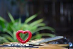 Le coeur en bois rouge a mis dessus la guitare pour l'amour sur le fond de nature Image libre de droits