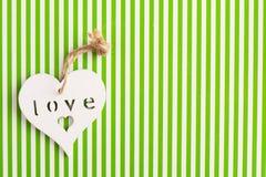 Le coeur en bois sur un vert blanc a dépouillé le fond Photographie stock libre de droits