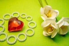Le coeur en verre rouge est entouré par des anneaux des perles et des fleurs de papier, cartes faites main Photo stock