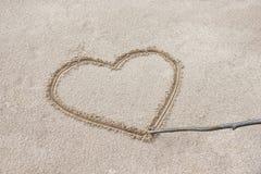 le coeur est dessiné sur le sable sur la plage avec un bâton Photos stock