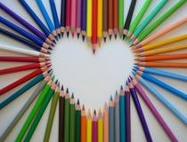 Le coeur est garni des crayons pointus en bois colorés lumineux sur le fond blanc Photos stock