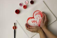 Le coeur est peint avec la peinture rouge sur une feuille de papier blanche Images libres de droits