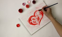 Le coeur est peint avec la peinture rouge sur une feuille de papier blanche Image libre de droits