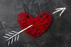 Le coeur est percé par une flèche d'un ange de l'amour Image stock