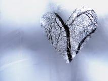 Le coeur est un symbole de l'amour sur une fenêtre congelée d'hiver Image libre de droits