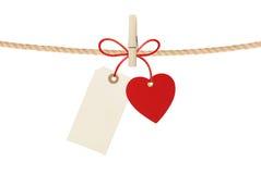 Le coeur et l'Empty tag de papier accrochent sur la corde d'isolement sur le blanc Photo libre de droits