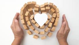 Le coeur et la main en bois de bloc se tiennent avec le concept de papier de coeur Photo libre de droits