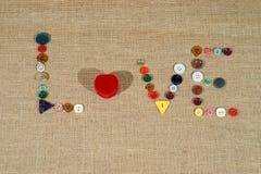 Le coeur et le mot aiment écrire avec les boutons de couture Image stock