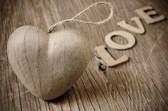 Le coeur et les lettres formant le mot aiment, dans la tonalité de sépia Photo stock