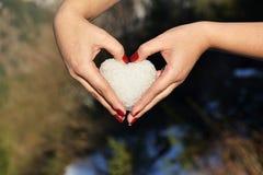 Le coeur fait avec la boule de neige dans des mains femelles, concept de jour de valentines Photo libre de droits