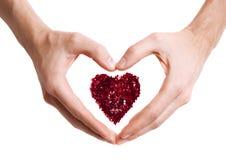 Le coeur fait avec le rouge miroite dans des mains dans la forme du coeur d'amour Photos stock