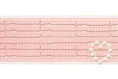 Le coeur fait de comprimés blancs de forme de coeur sur ECG de papier résulte Image libre de droits
